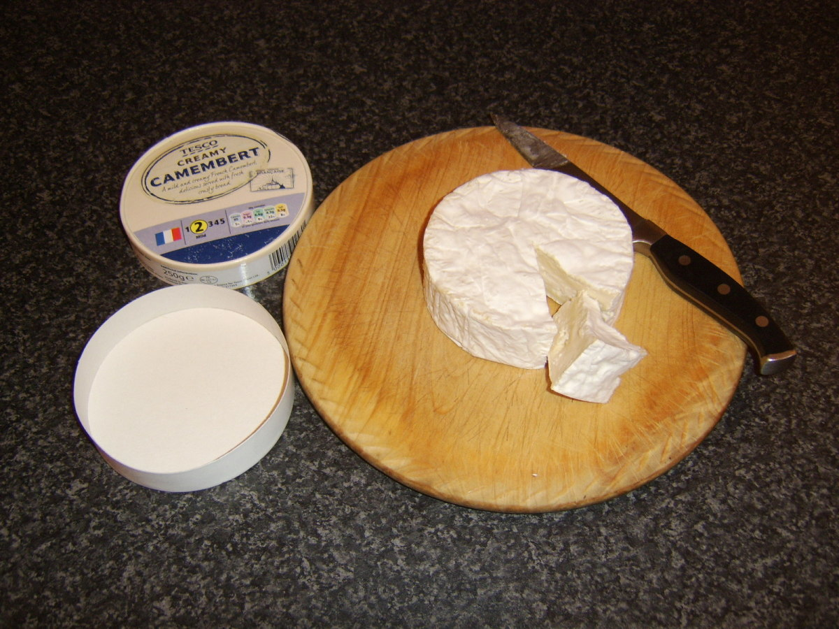 Wedges of camembert are cut to accompany the fresh fruit