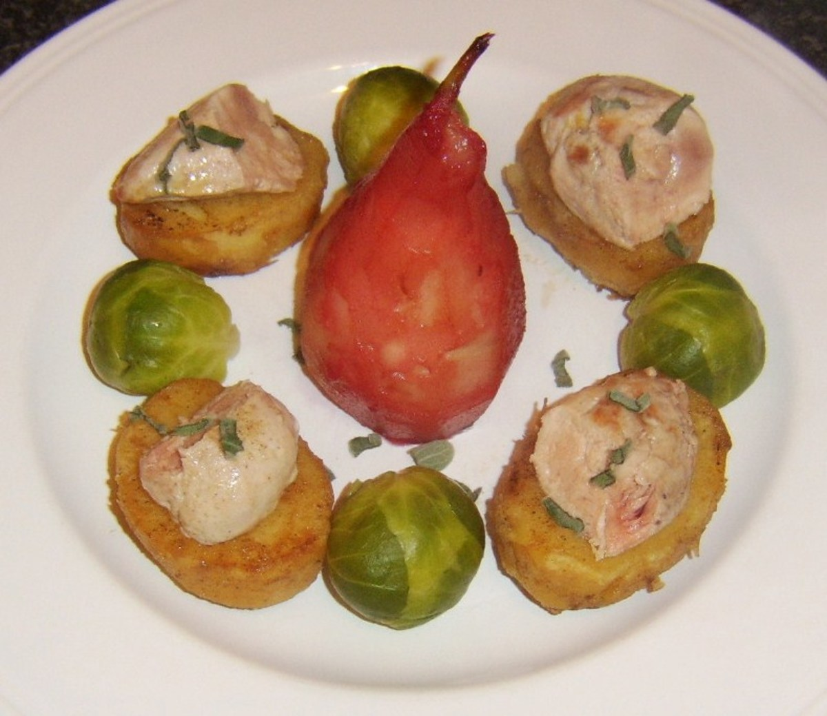 Pan fried partridge breasts are halved and served on fondant potatoes with a pear poached in cranberry juice centrepiece