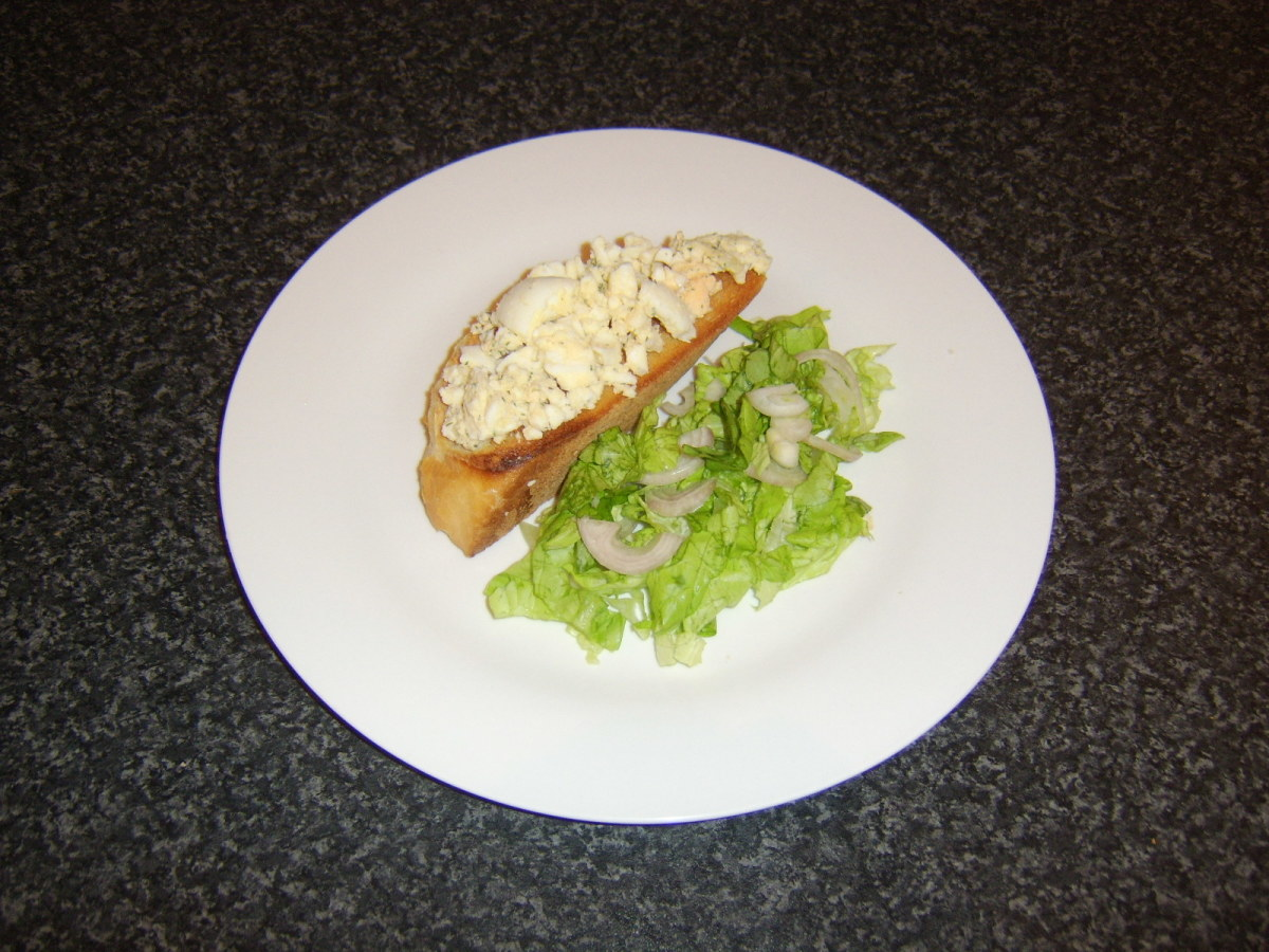 A hard boiled egg, mashed with herb butter and served on warm toast with a simple salad