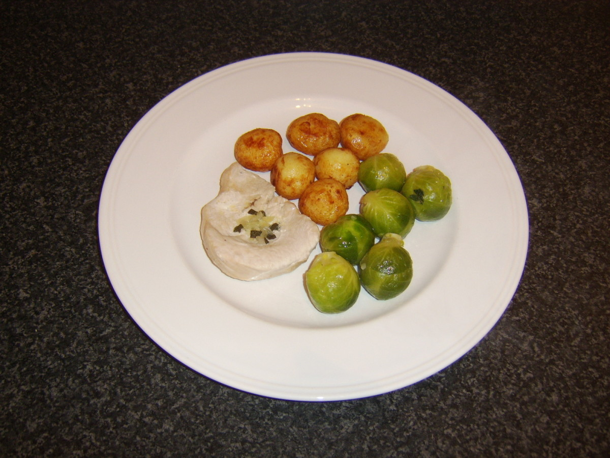 Turkey breast fillet is baked with sage and onion butter and served with roast potatoes and sprouts