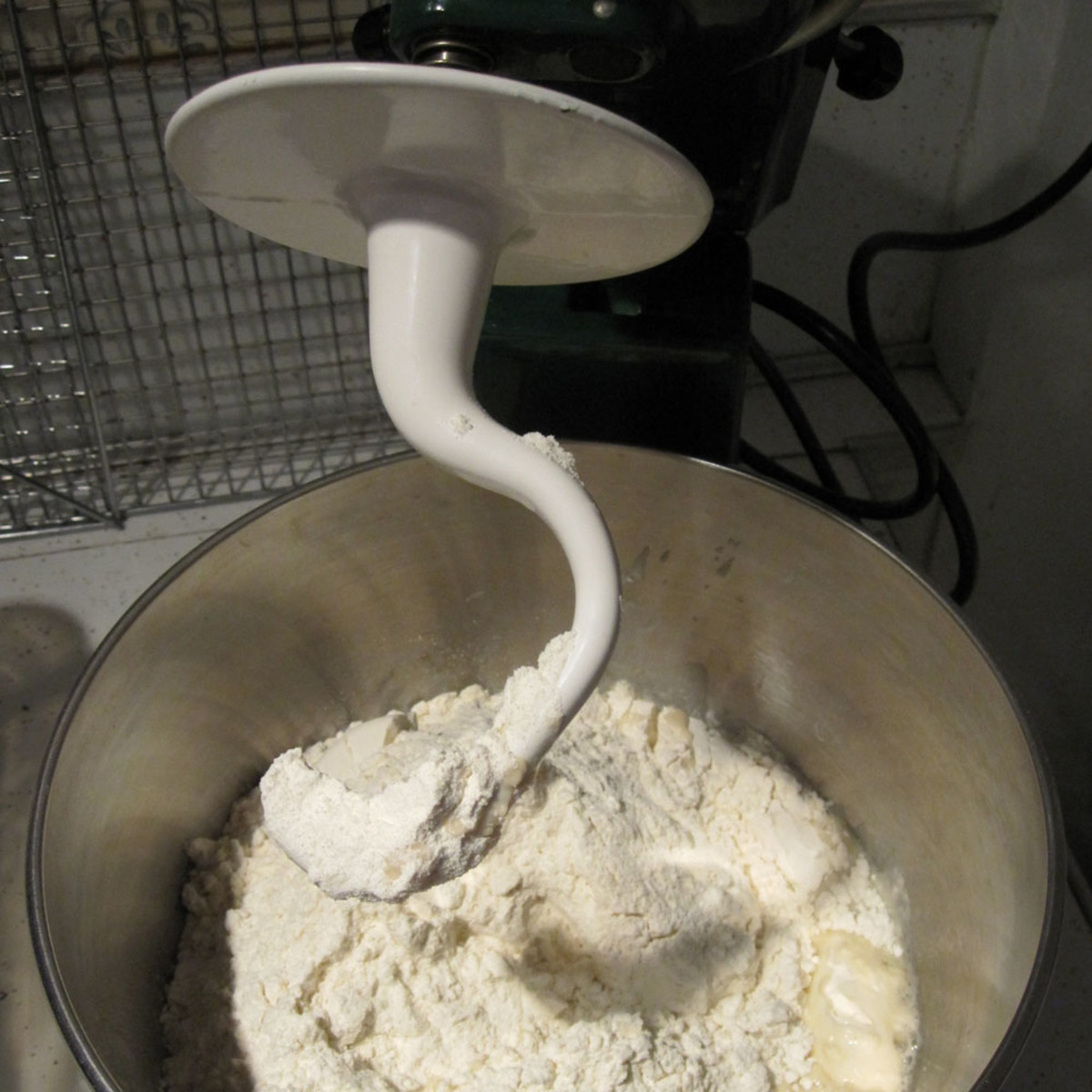 KitchenAid mixer with dough hook and bowl inserted.