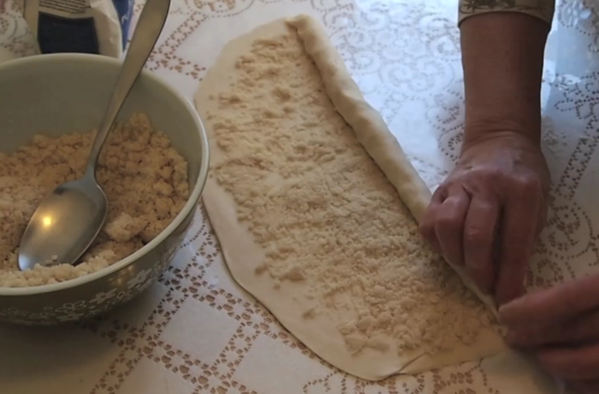 Rolling the pastry, with the filling spread across.