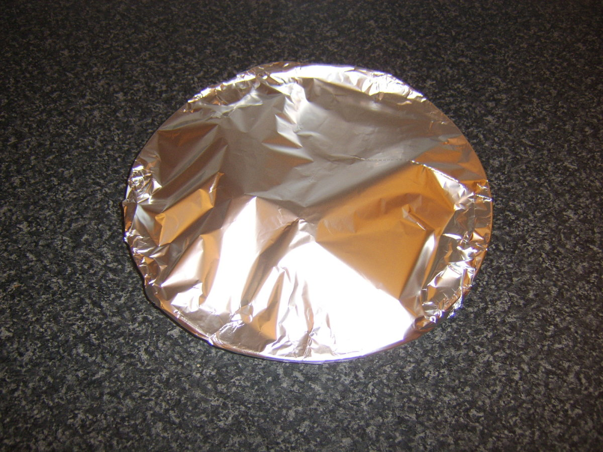 Pork chop is covered with foil to rest