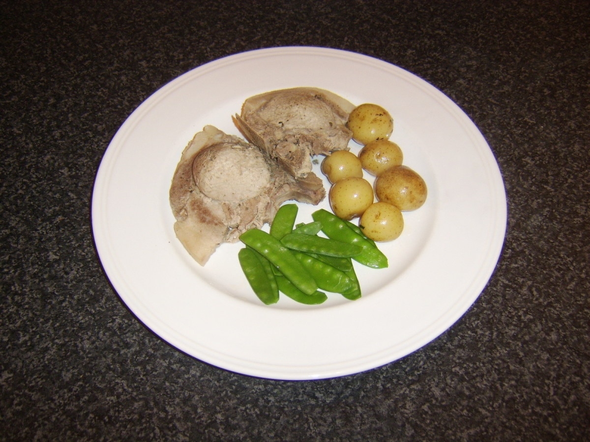 Casseroled pork chops are served wwith herb buttered baby new potatoes and blanched mangetout