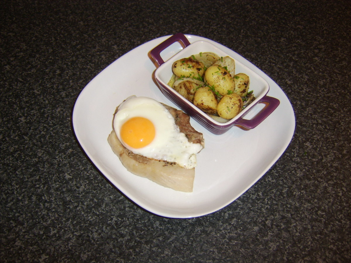 Pork chop baked in the oven in foil and served with spicy fried potatoes and onions and a fried egg