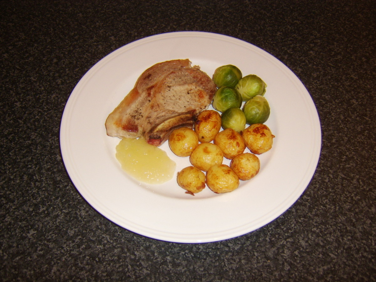 Pork chop shallow fried in oil and served with roasted baby potatoes, Brussels sprouts and apple sauce
