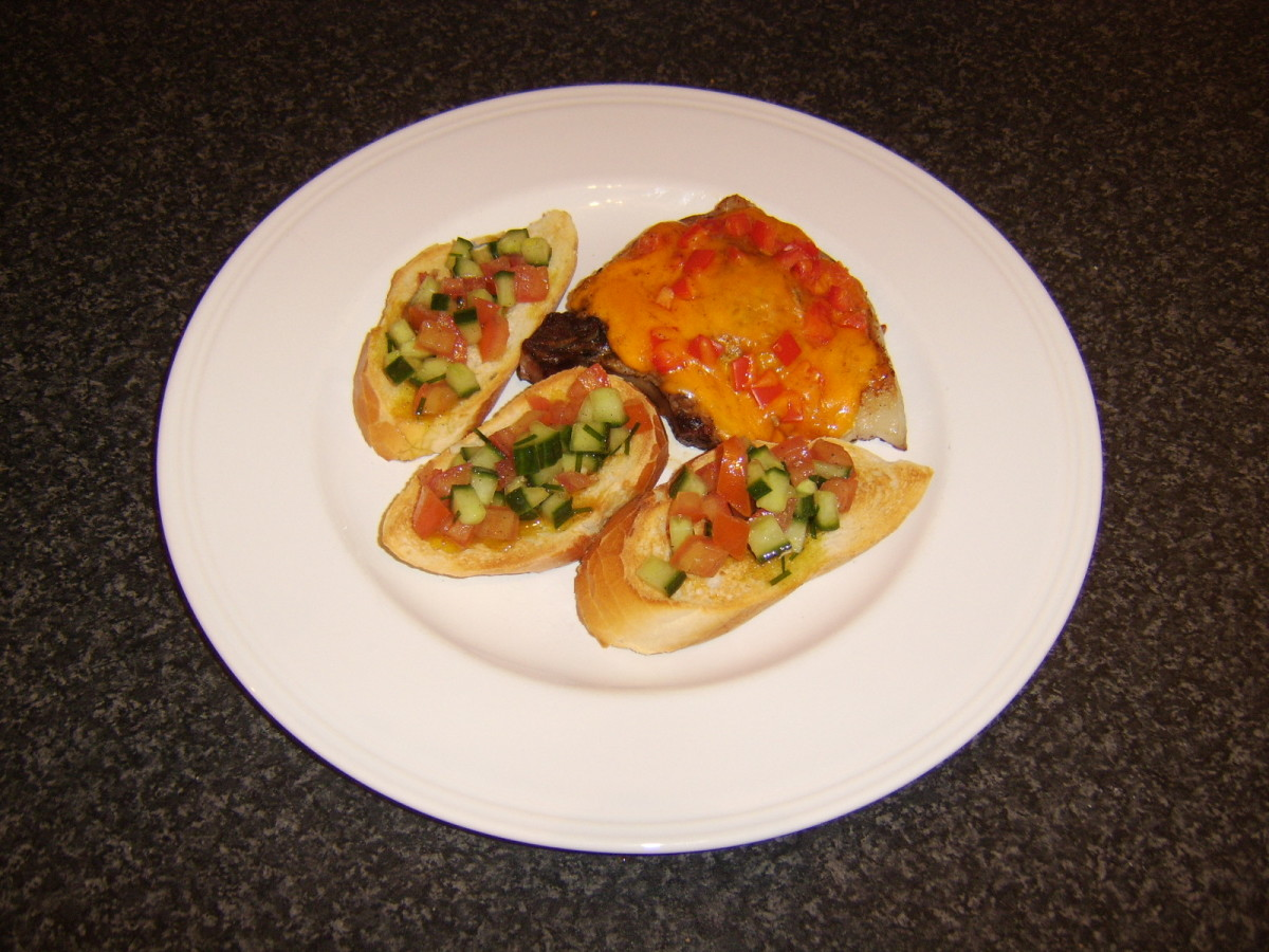 Cheese and chopped red bell pepper are melted over a pork chop which is then served with salsa based bruschetta