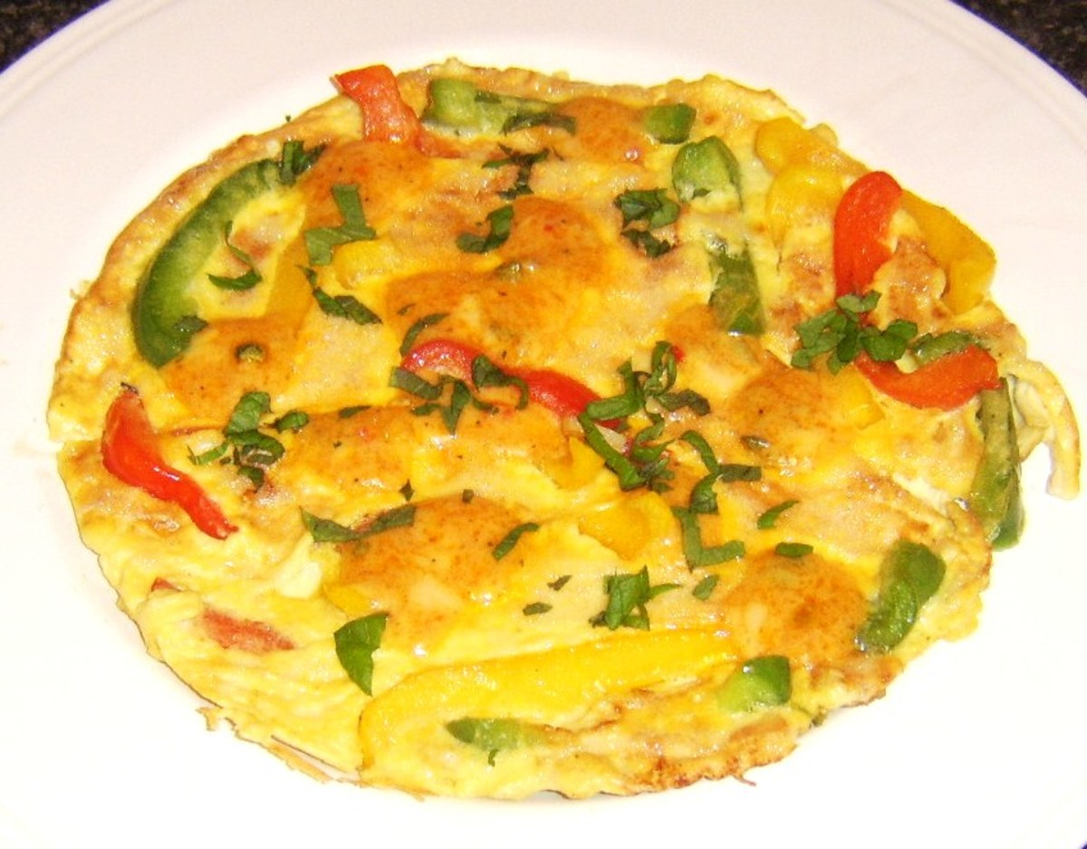 Duck egg frittata with bell peppers is topped by Mexicana cheese and garnished with fresh basil