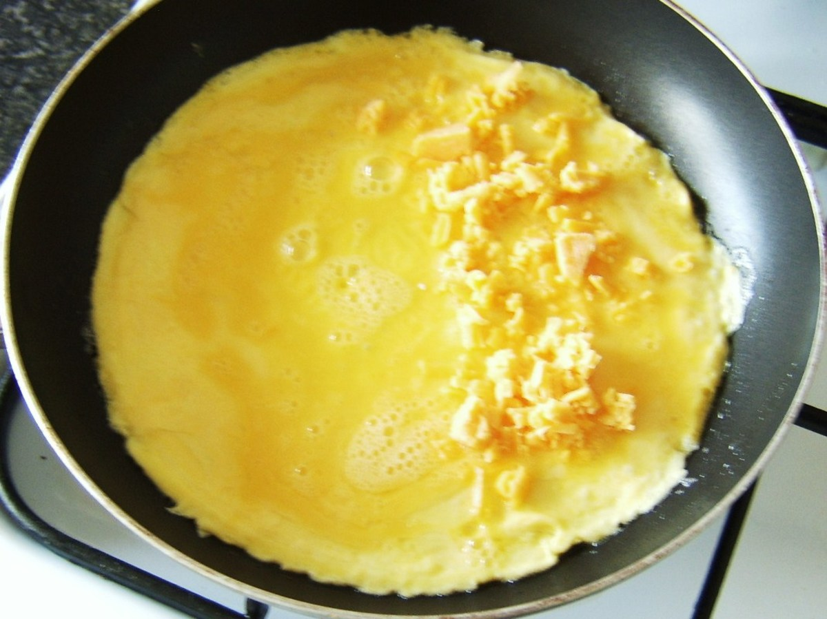 Cheese is scattered on half of duck egg omelette