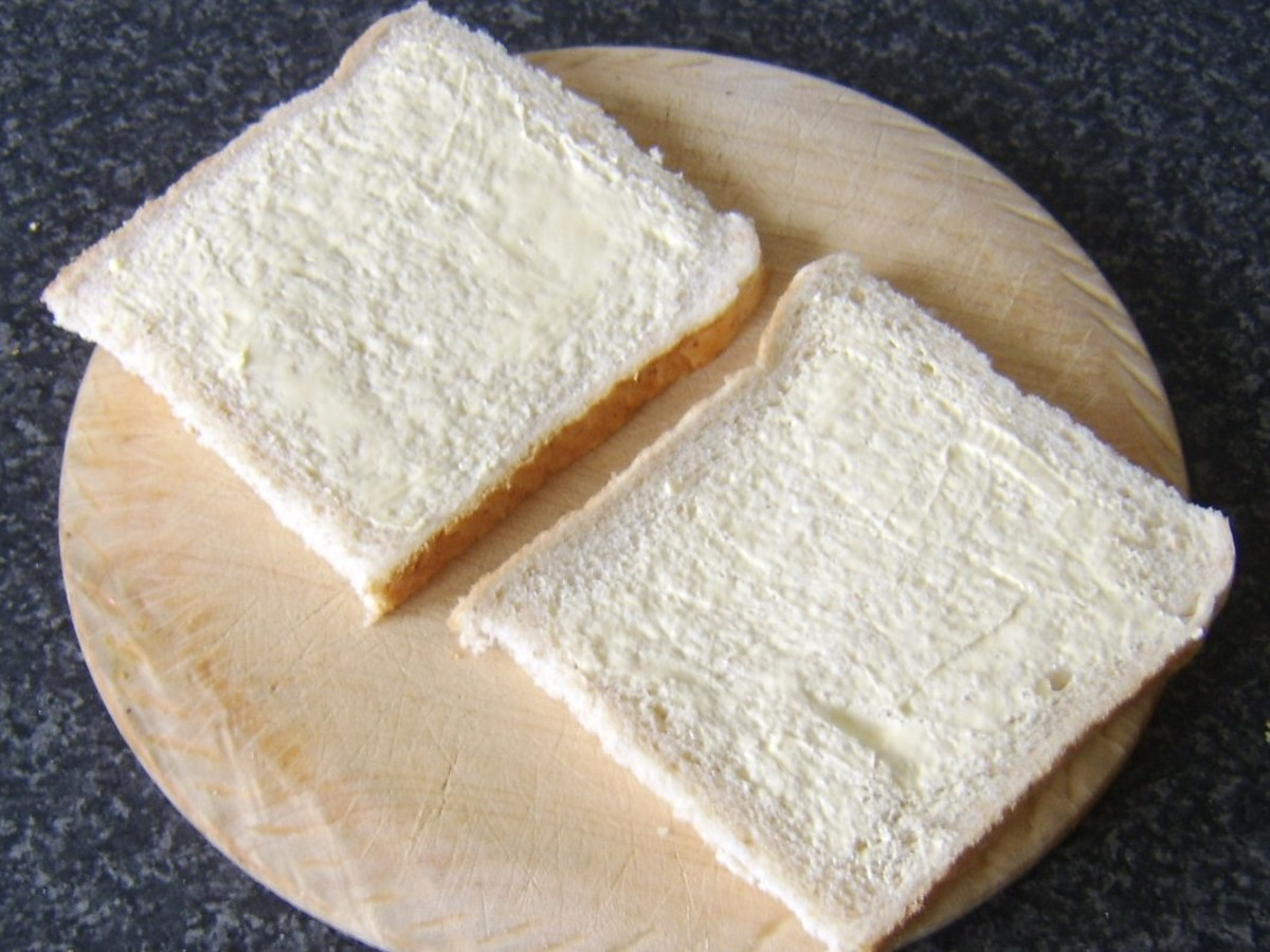 Bread is buttered for toasted sandwich