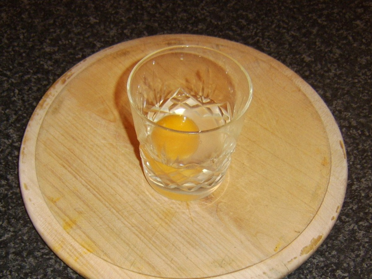 Duck egg is carefully broken in to drinking glass