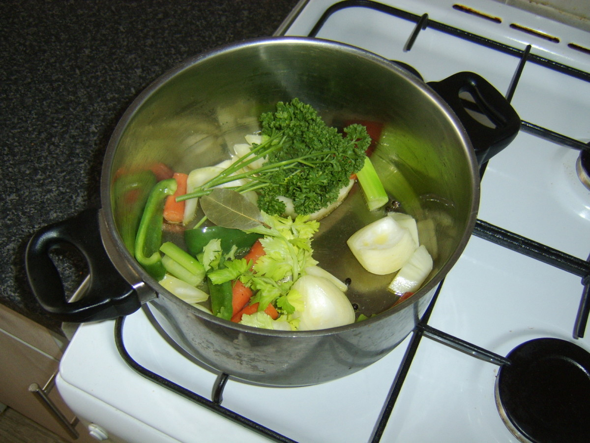 Herbs and peppercorns are added to the sauteed vegetables