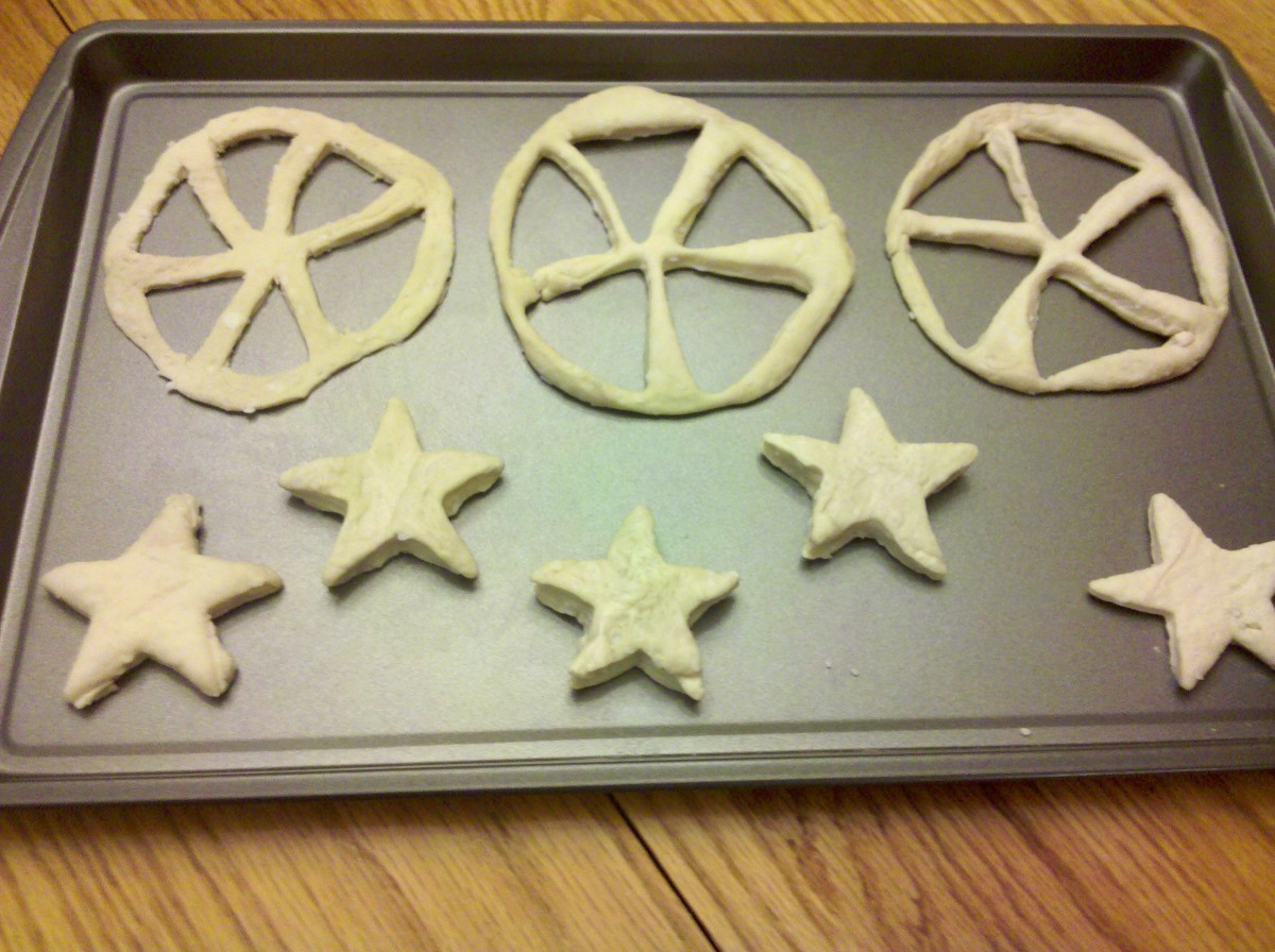 Use triangle cookie cutter or knife to cut out spokes of wheel. We also cut out star shaped biscuits with the scraps of the wheel.