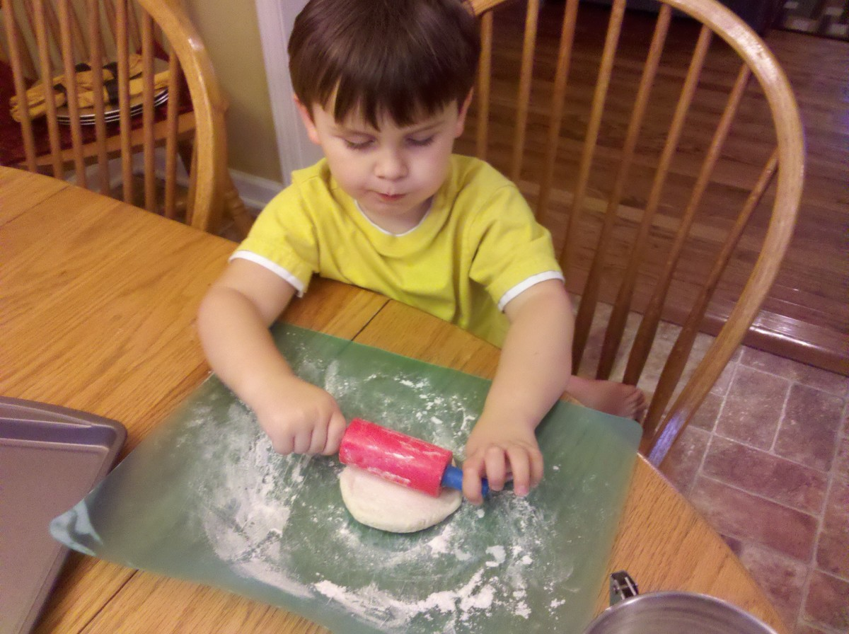 Rolling out the biscuits with a rolling pin.