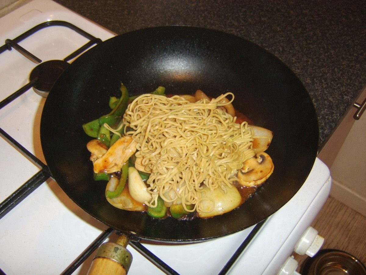 Noodles are added to sweet and sour stir fry and stirred through