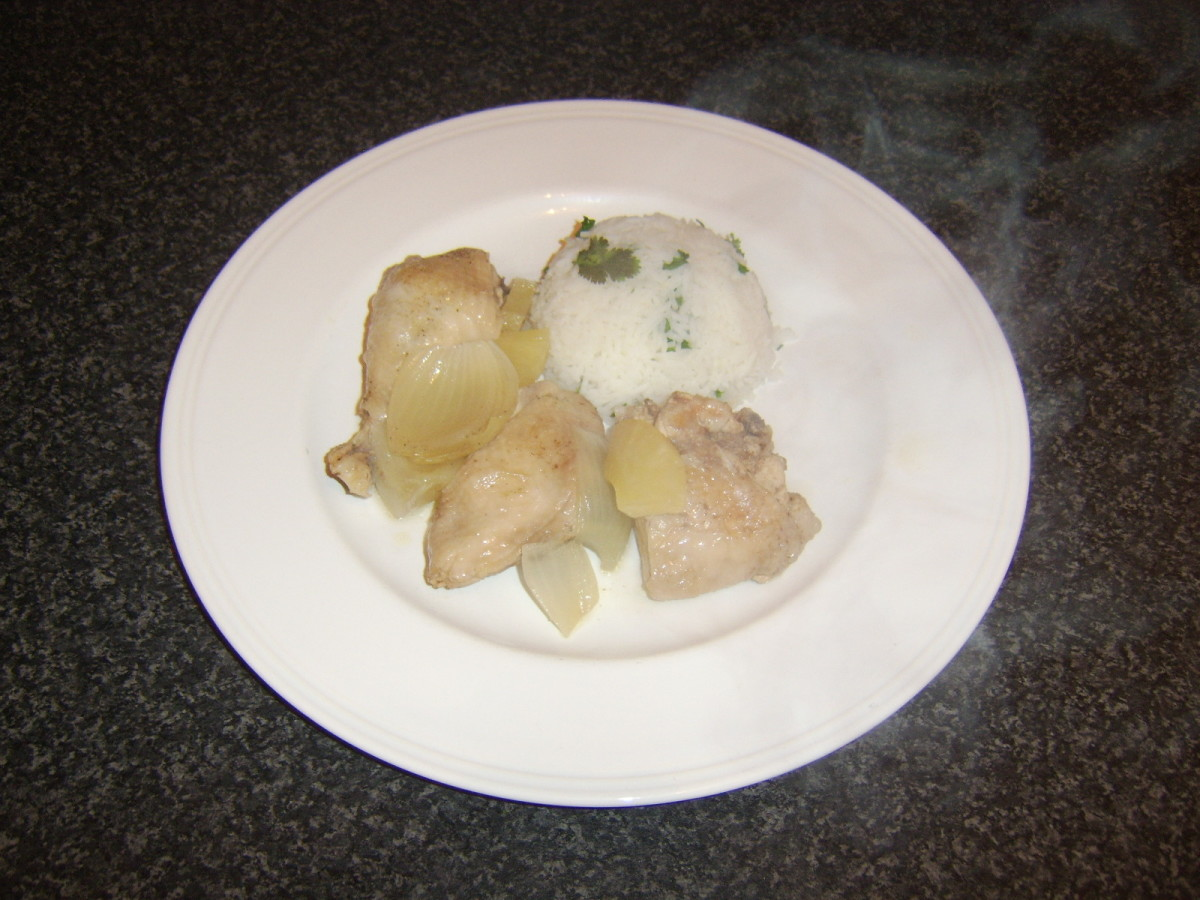Chicken, pineapple and onion are plated alongside the rice