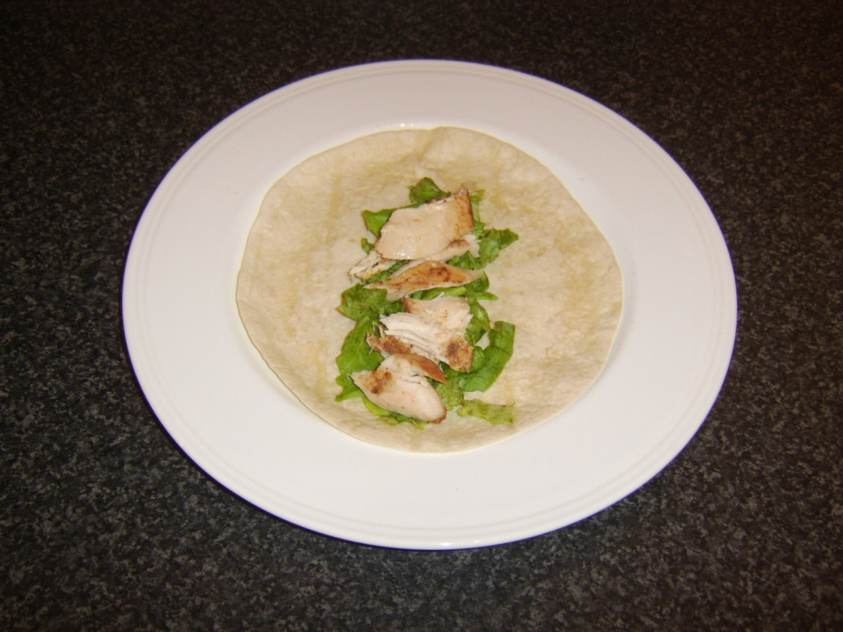 Pieces of leftover tandoori chicken are laid on a bed of lettuce on a tortilla wrap