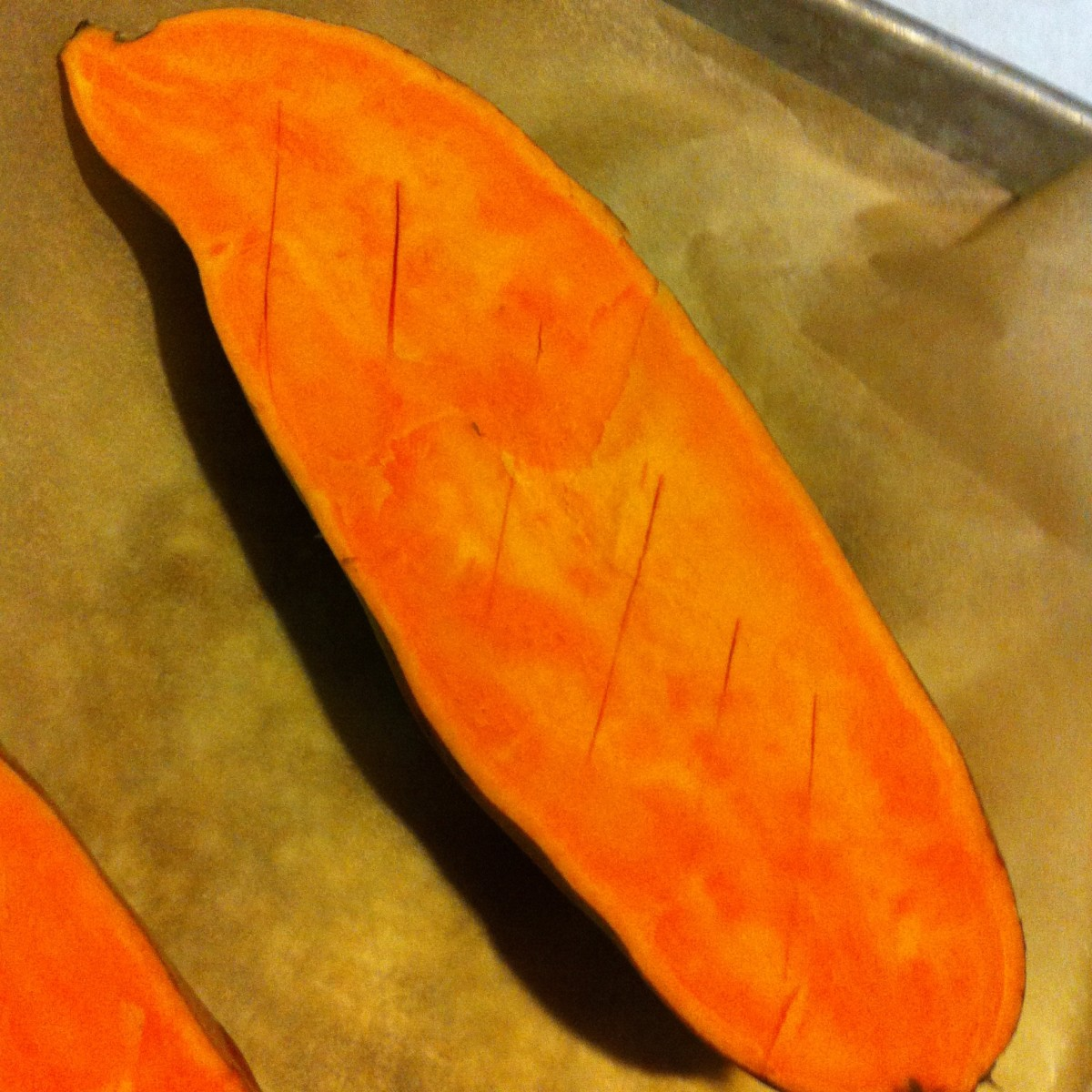 A sweet potato before cooking: the interior flesh has been scored in order to expose more of its surface area to heat while roasting.