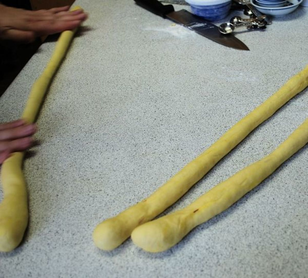 "Separate dough into three pieces and roll into long ""snakes."""