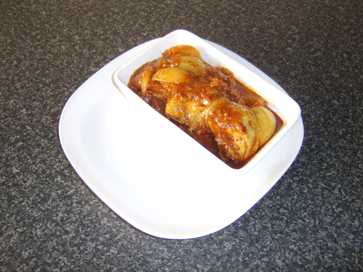 3 chicken thighs and sauce are added to a dish and the serving plate