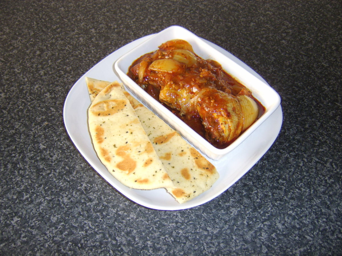 Naan bread is sliced and plated with the Jalfrezi chicken thighs