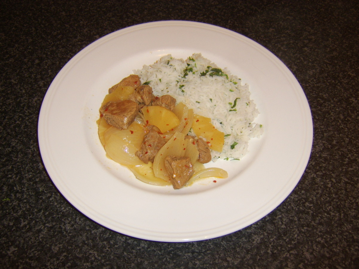 Spicy pork and pineapple casserole is spooned over the rice