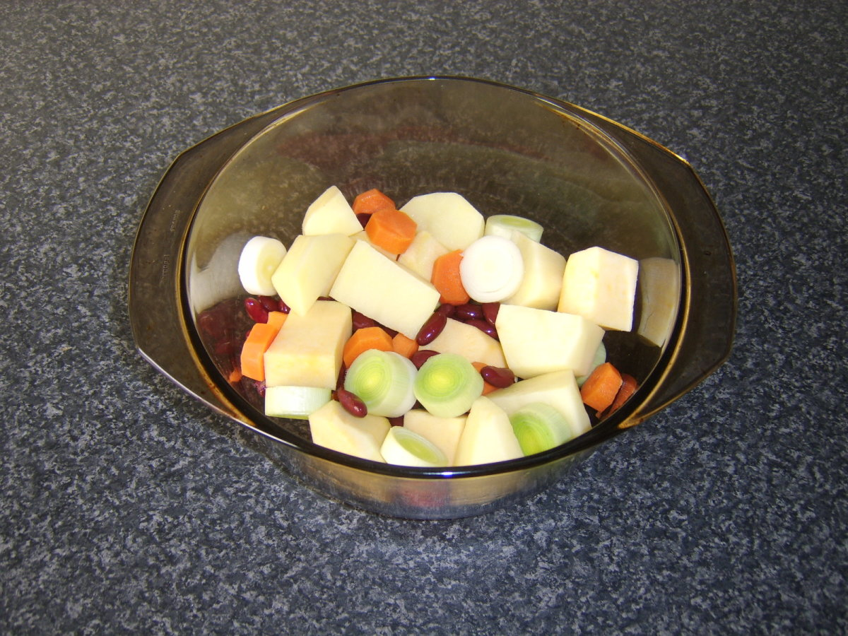 Vegetables and beans are stirred together in casserole