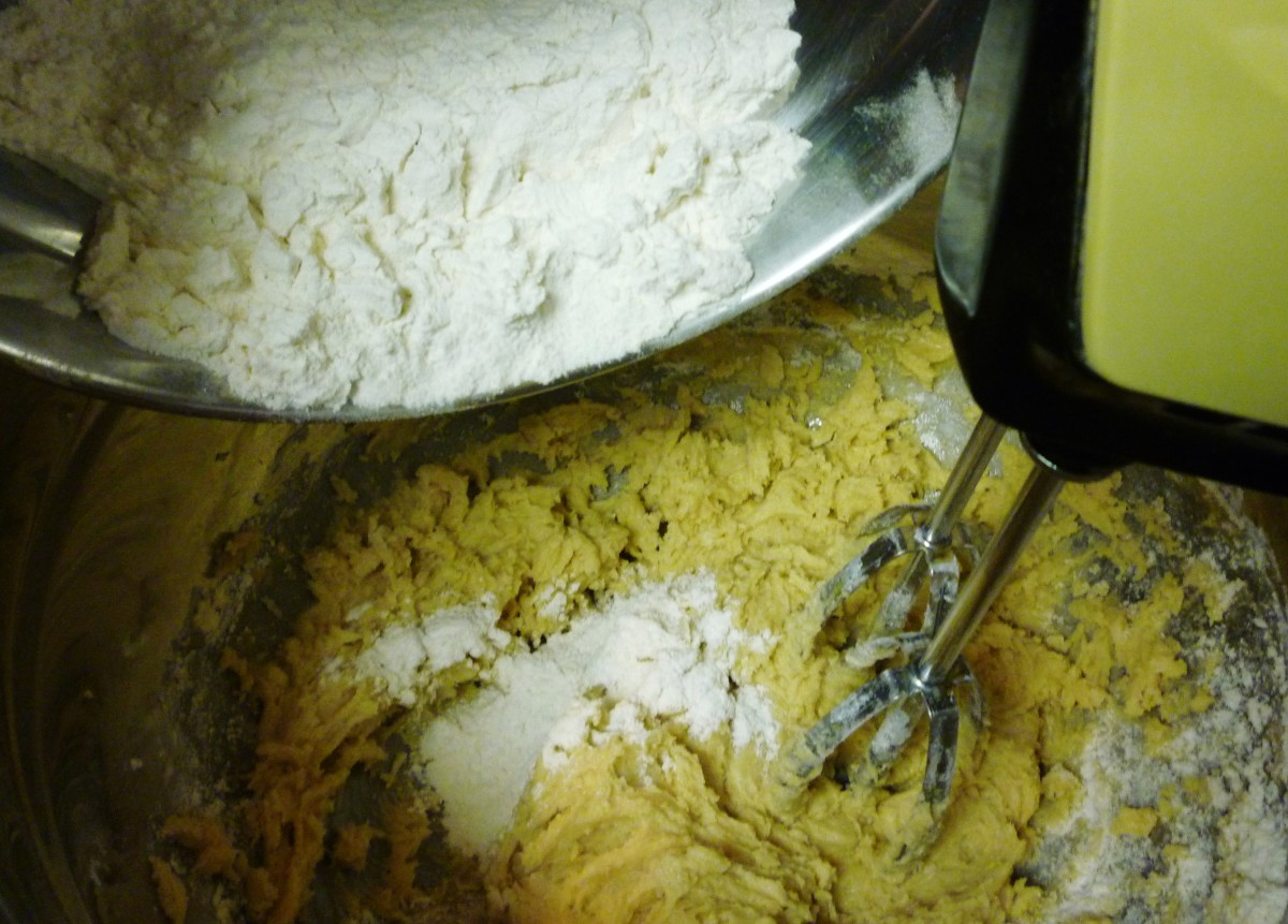 Adding the sifted ingredients alternately with the dissolved baking soda into the creamed mixture.