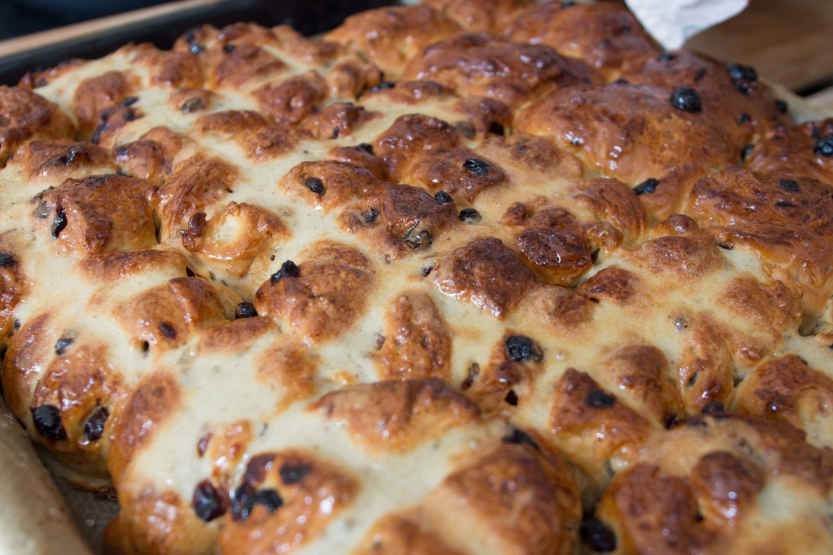 Cooked and glazed fruit buns (back of tray) and hot-cross buns.