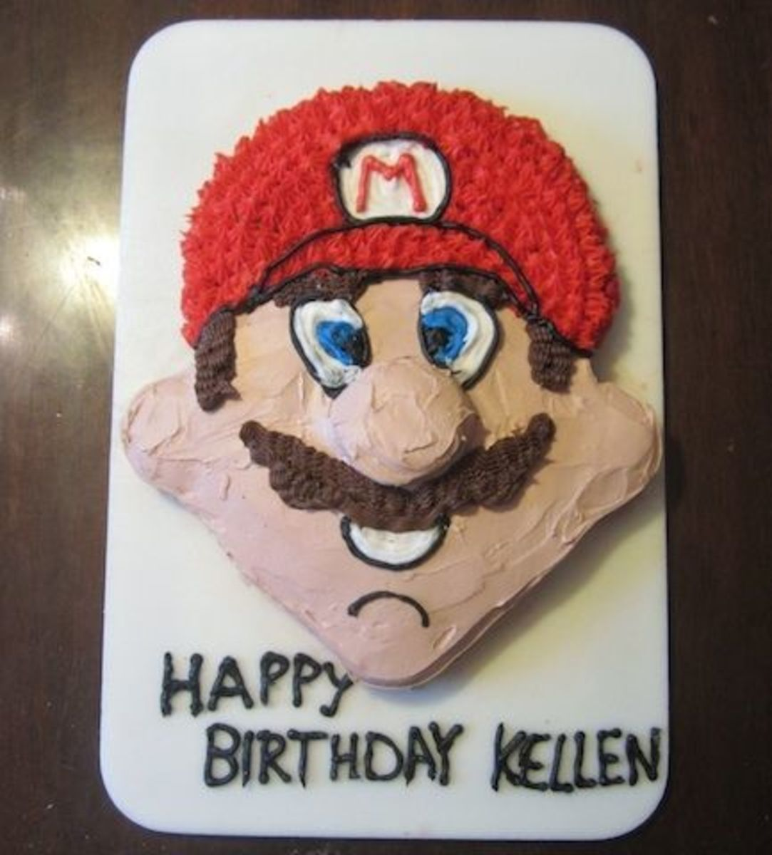 I used black icing to outline the hat brim and logo, eyes, mouth, and chin.