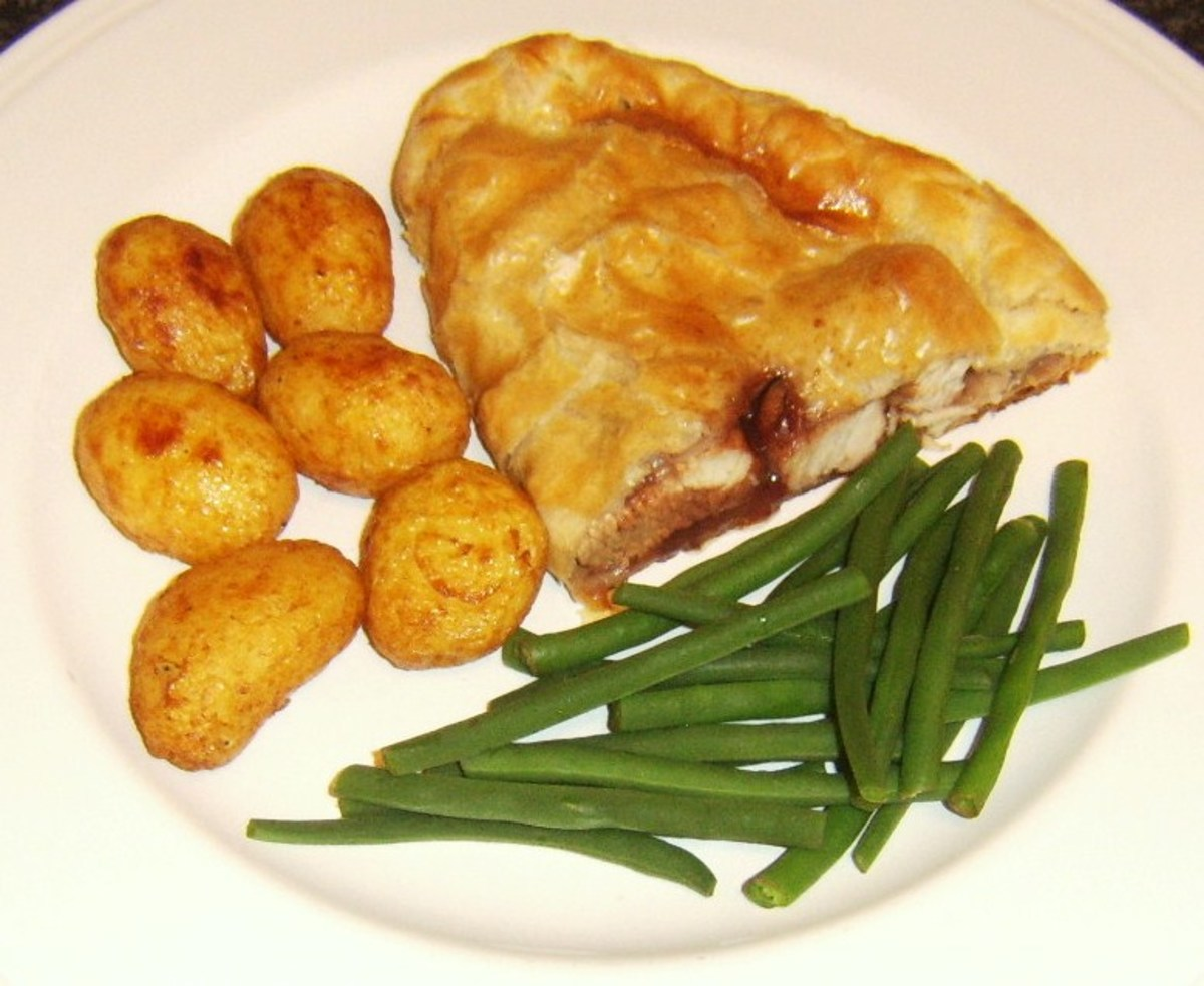 Turkey, sage and onion pasty with cranberry and port sauce is served with roast potatoes and trimmed green beans