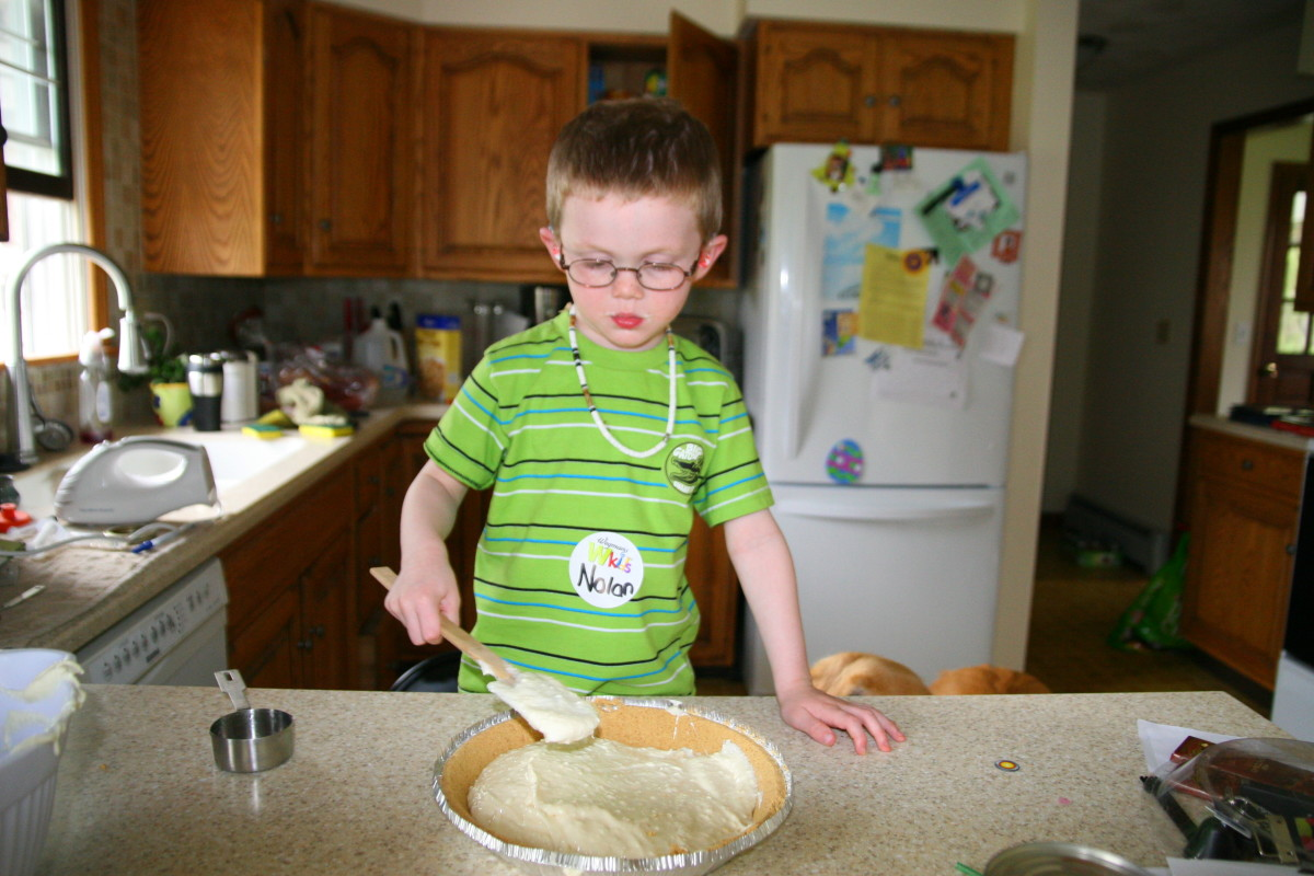 Spreading the pie filling helps develop fine motor skills - yet another way that cooking is a wonderful activity for kids!