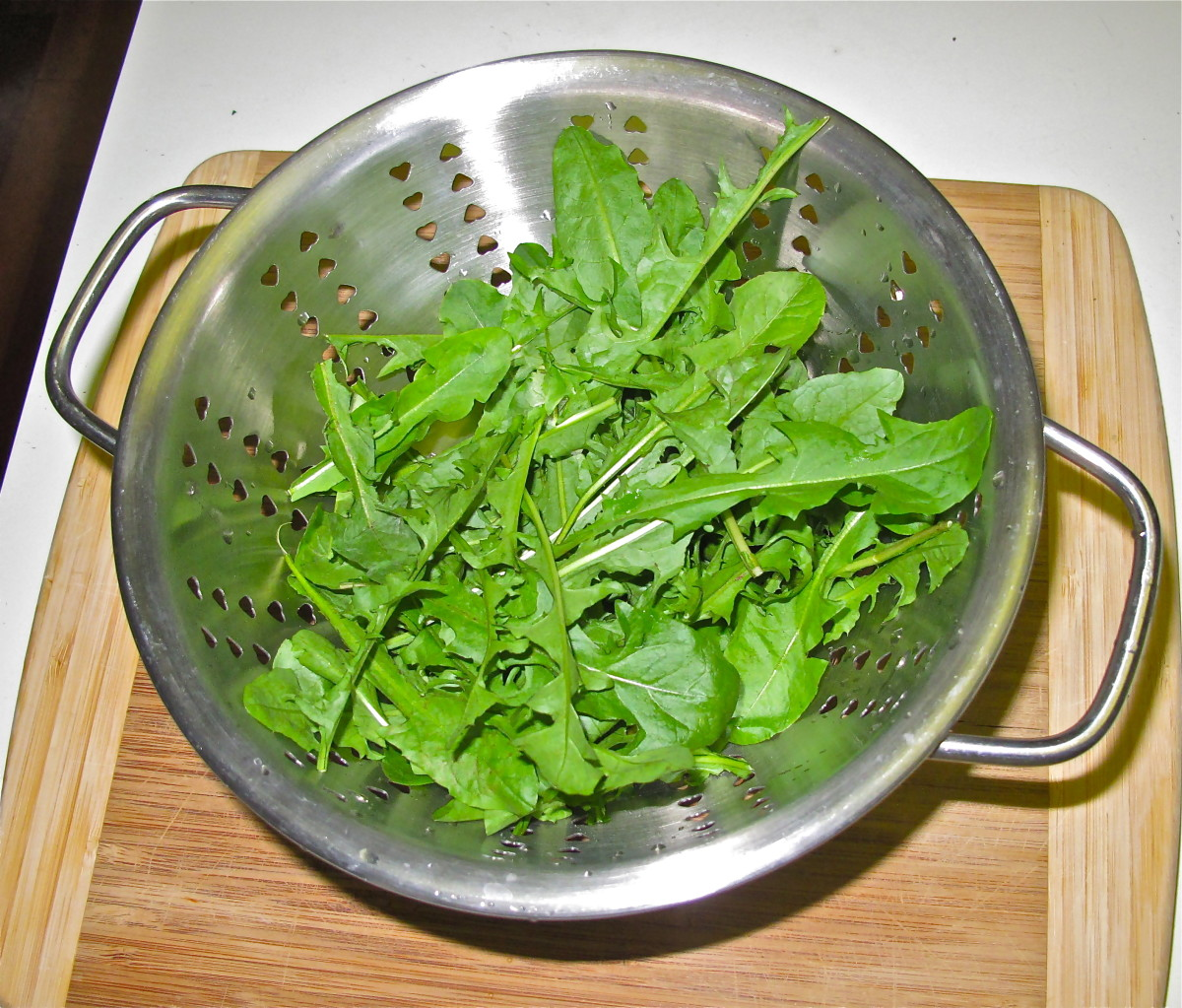 Rinse and clean fresh, tender leaves from dandelion plants.