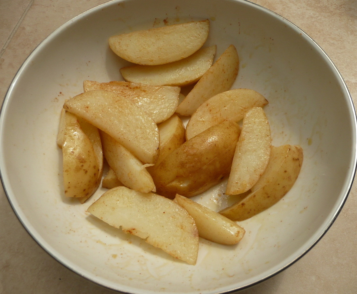Making potato wedges—mix all ingredients together to evenly coat.