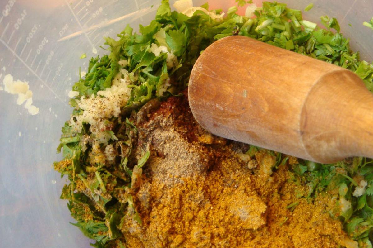 Add squeezed garlic, khmeli suneli, vinegar, pepper, adjika, and pestle everything