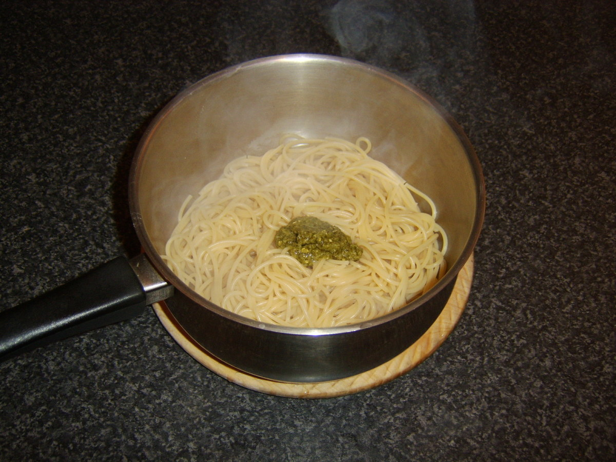 Green pesto sauce is stirred through drained spaghetti