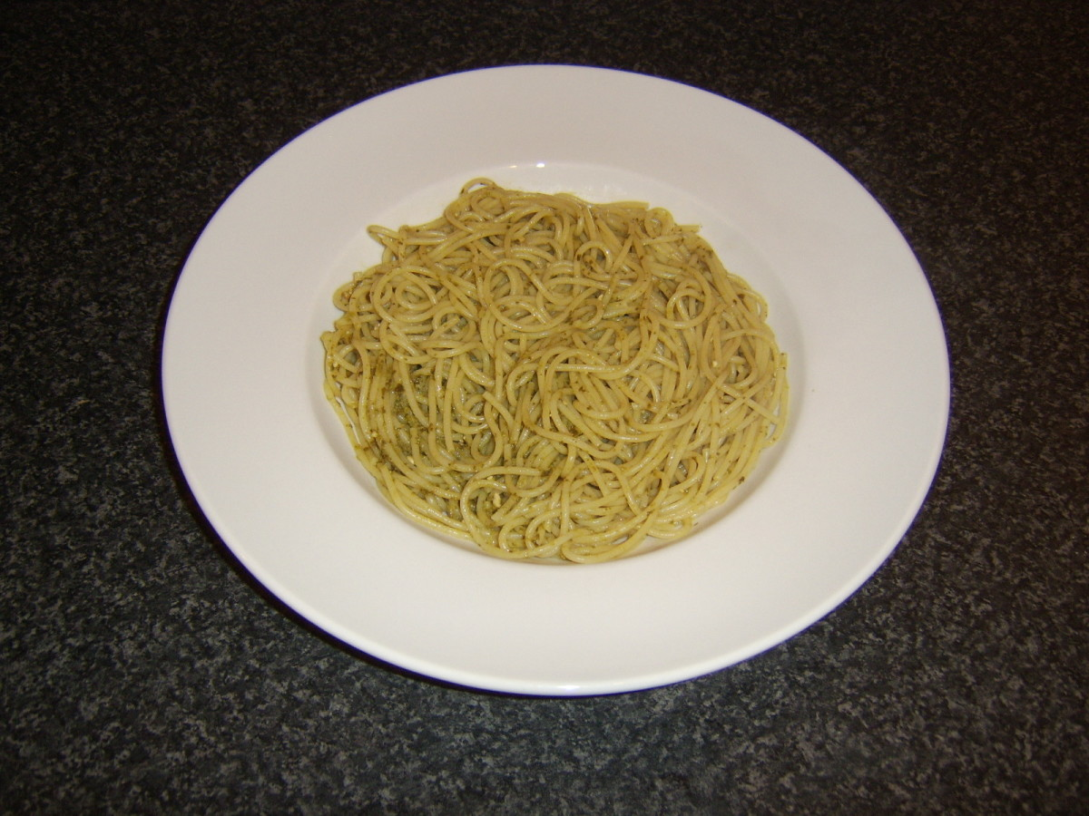 Spaghetti and green pesto sauce is laid in the bottom of a deep serving plate
