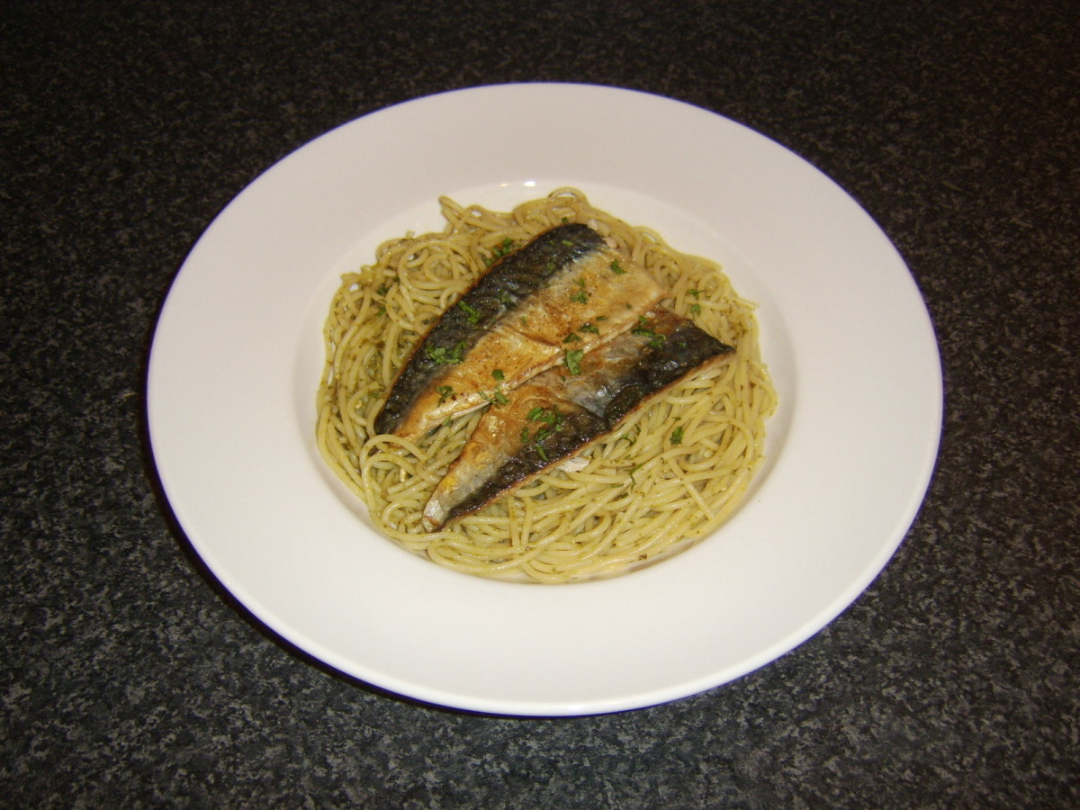 Spaghetti is cooked as normal before being stirred with green pesto sauce and topped with quickly fried mackerel fillets