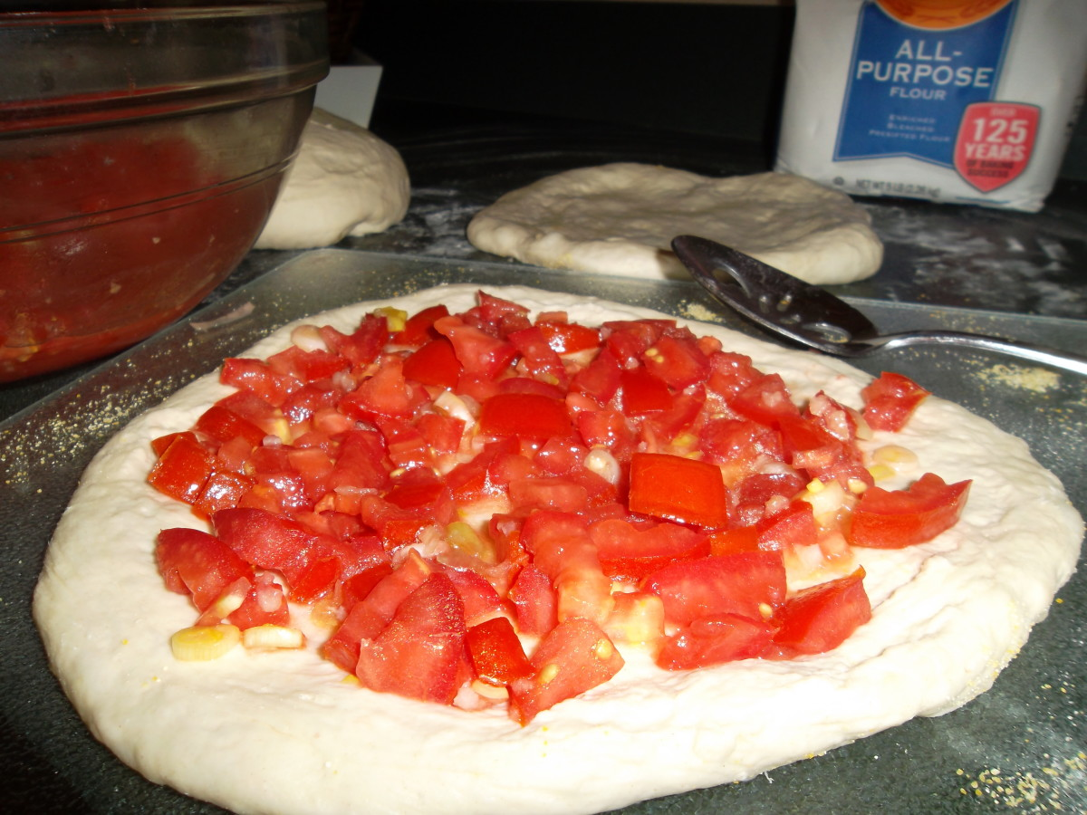 Put tomatoes on the pizza dough.