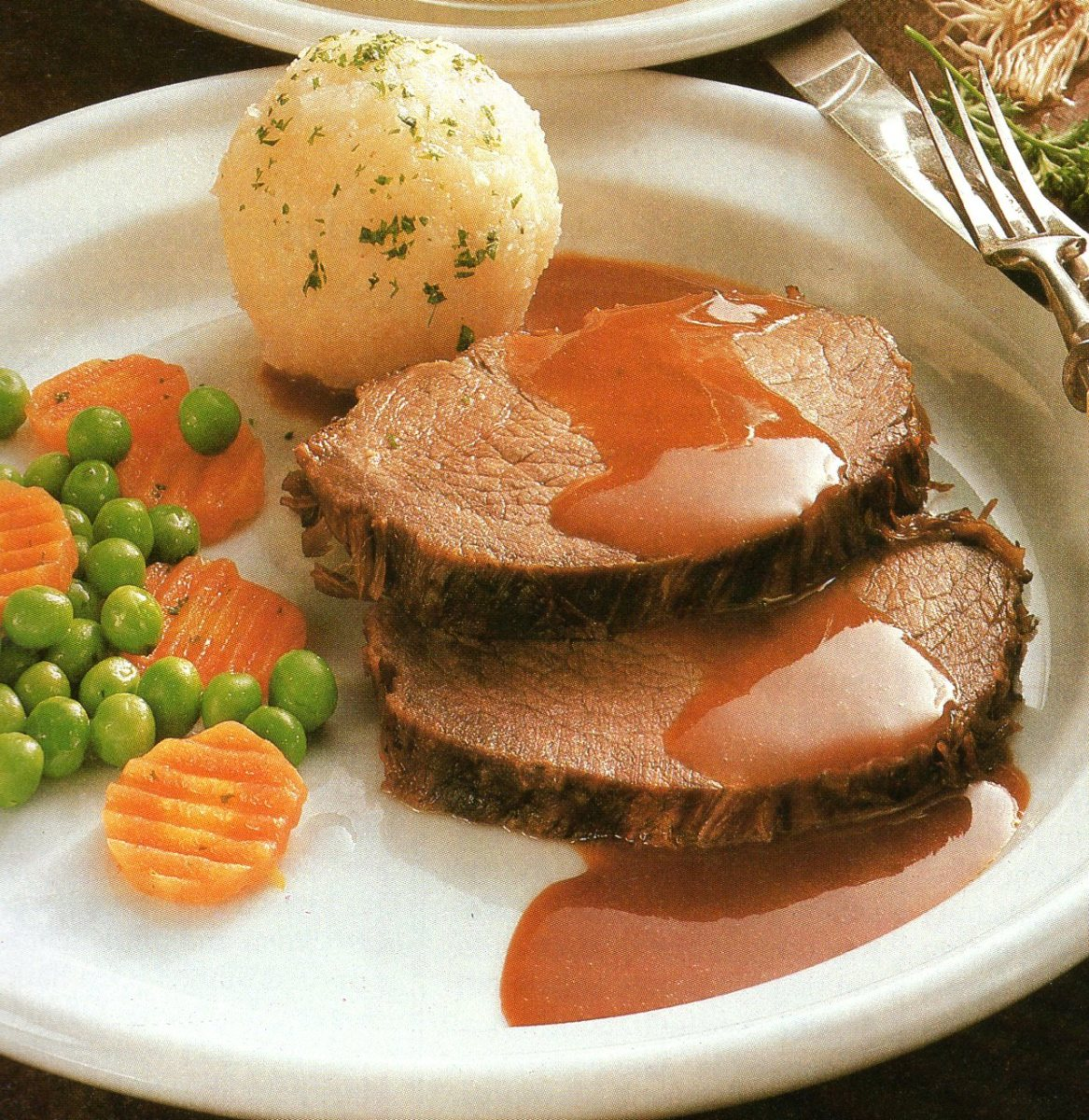 One big Kloss, peas and carrots served with Sauerbraten.