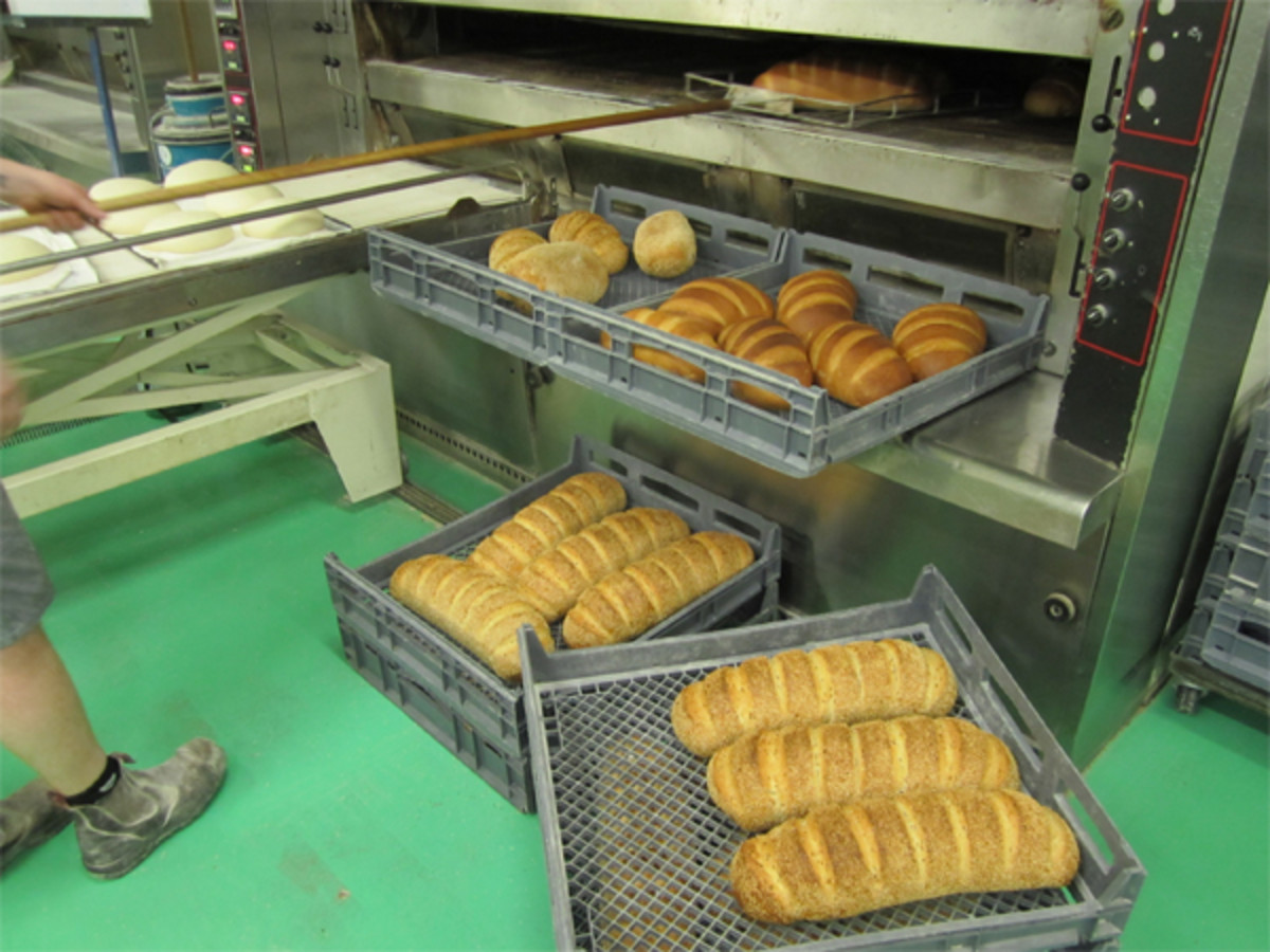 Freshly baked loaves are transferred directly onto delivery trays. Notice the next batch of loaves lined up behind ready to go in.