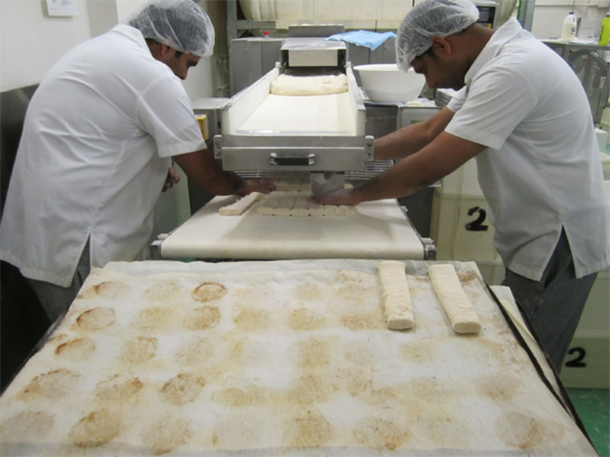 Portions of croissant dough that have been hand-portioned from the dough that has been rolled out by the machine.