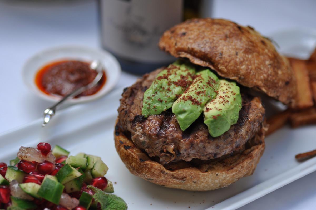 Sumac Lamb Burger on Rosemary Buns. Accompanied with pomegranate, cucumber, lemon and mint salad; home made chips; and harissa. Image: © Siu Ling Hui