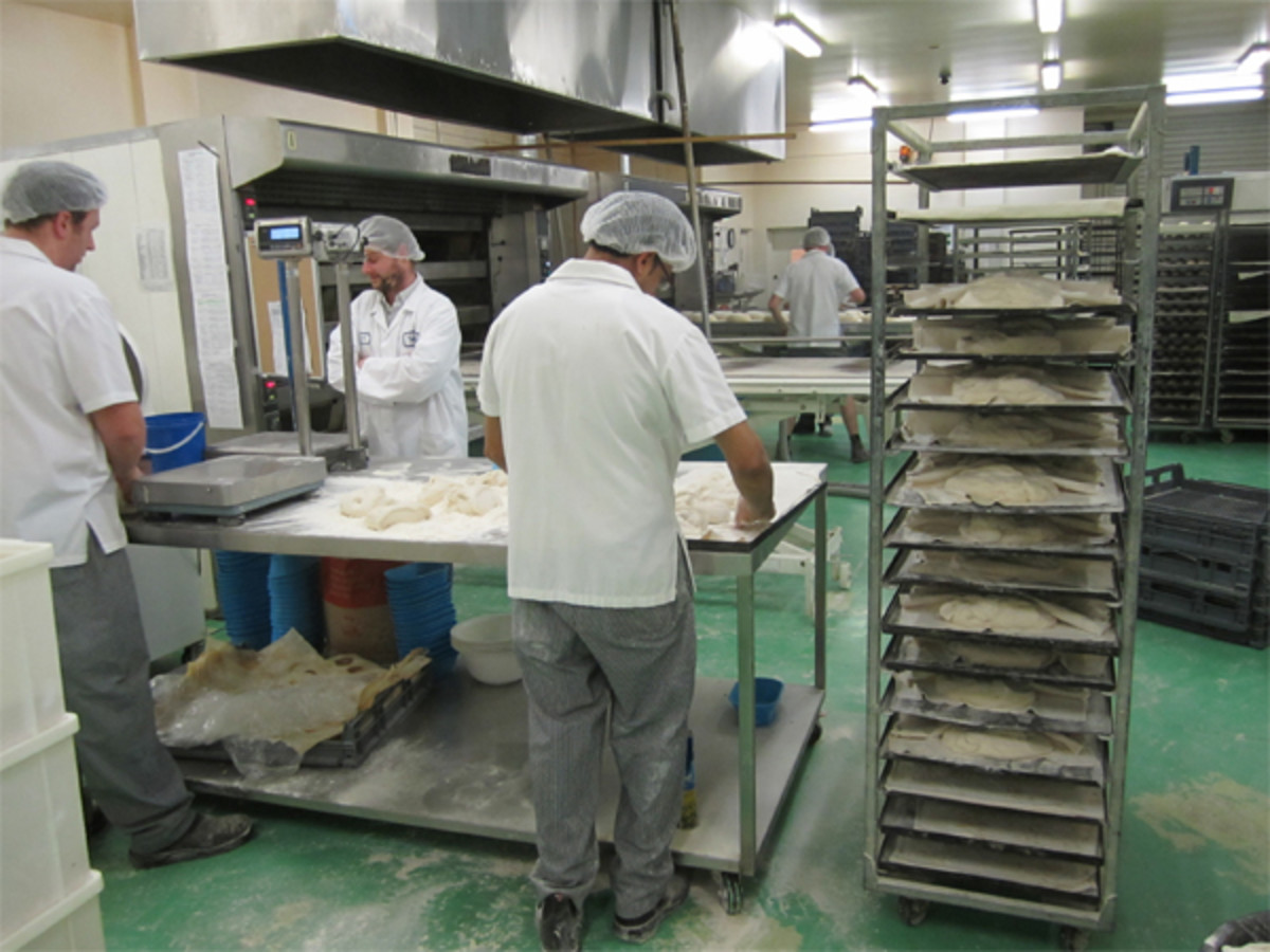 Loaves being shaped to be placed on trays on racks for final rise.