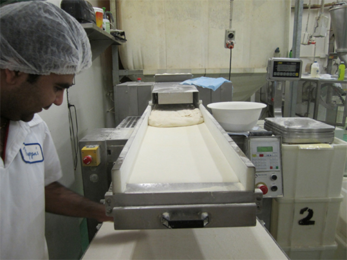 Croissant dough is rolled out on a special machine. The bakers hand-cut them into portions at the end.