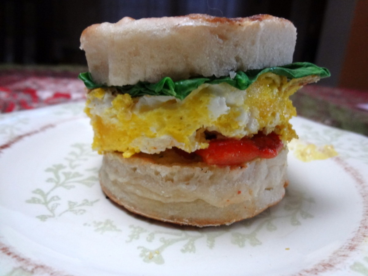English muffin sandwich with egg, roasted peppers, and spinach