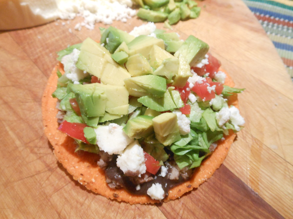 A beef tostada includes black beans, thinly sliced steak, shredded lettuce, chopped tomato, crumbled queso fresco, and chunks of avocado.