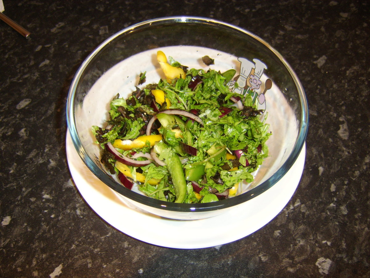 Salad is tossed with salt and pepper