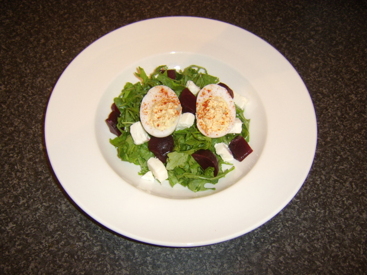 Deviled duck eggs are placed on top of beetroot and feta cheese salad