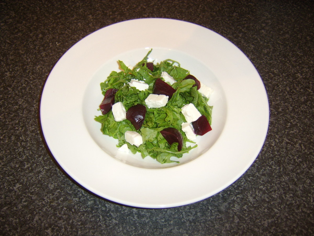 Beetroot and feta cheese are added to bed of green salad leaves
